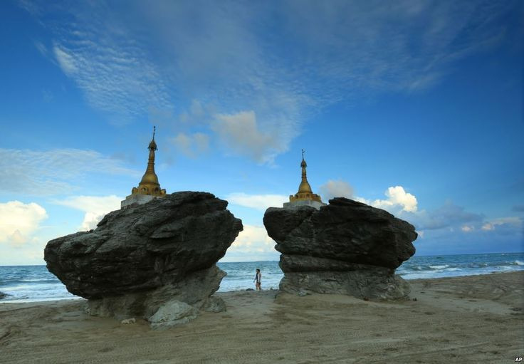 Two men walk past pagodas at Ngwe Saung beach, Pathein township, about 145 miles from Yangon, Myanmar.