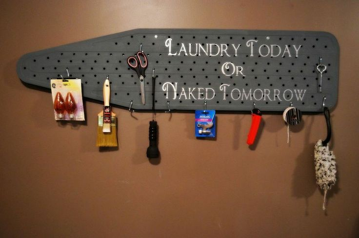 Clever! Ironing board repurposed as a pegboard for laundry room storage.