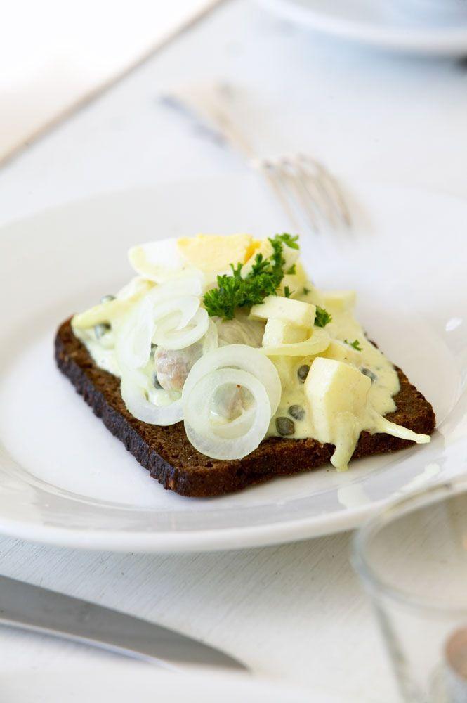 Et stykke groft rugbrød med karrysild -  en opskrift på et klassisk dansk stykke smørrebrød.