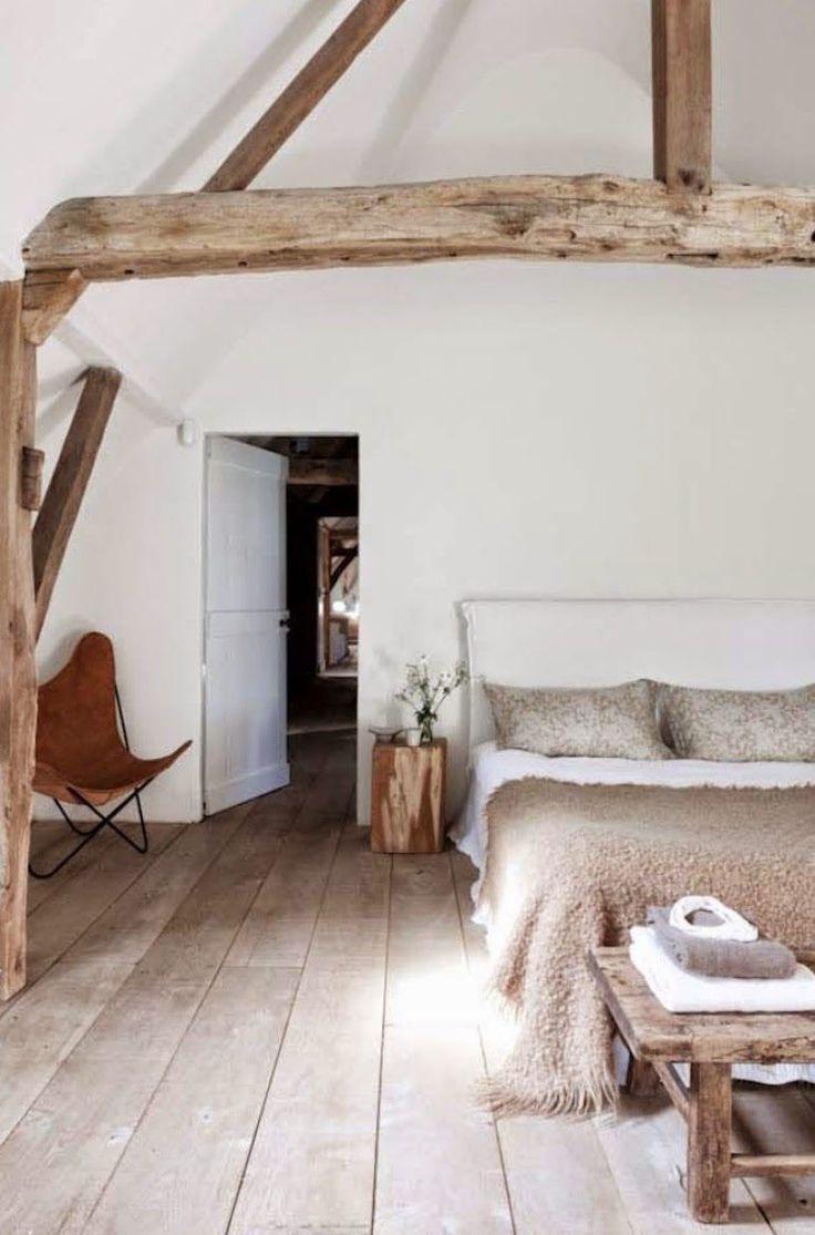 chambre mansardée de style rustique décorée de poutres apparentes, une chaise papillon en cuir marron et une literie beige