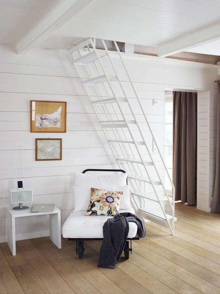 SPENSTIG TRAPP: Trappen opp til sovehemsenetegnet og bygget avbestefaren da han eide hytta.Avslapningsstolen er fra Palma.Bildene er gamle kart, blomstretpute fra Missoni. På gulvet erdet brede planker i eik.Styling: Tone Kroken.