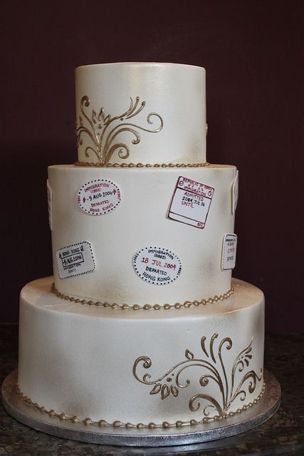 The classic white wedding cake would be embellished with passport stamps and metallic piping