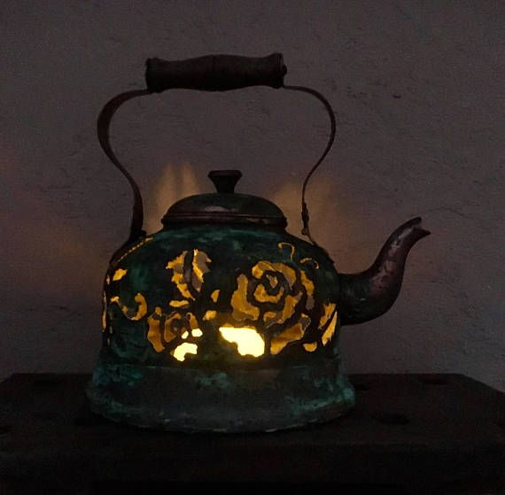 Antique copper tea kettle hand-cut with a plasma torch with floral designs. Illuminated with a flameless candle and finished with a turquoise patina. Wooden handle and lid knob.  -9 Inches in height including handle -8 1/2 inches wide  -flameless candle included
