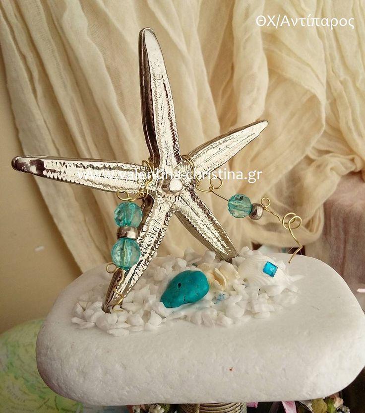 Μεταλλικός αστερίας πάνω σε βότσαλο με κοχύλια
