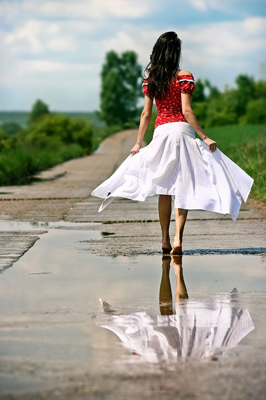 Beautiful woman in bare feet after rain