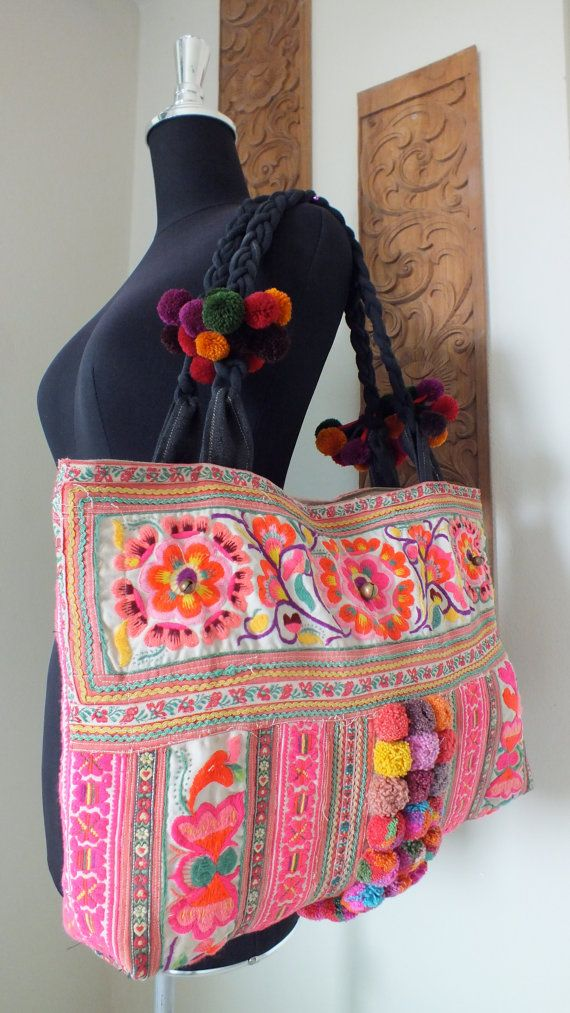 Ethnic bag with pompoms and embroided flower decoration.