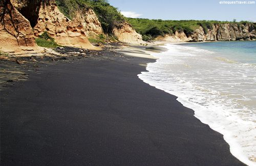 VIEQUES' BLACK SAND BEACH  Vieques is filled with beautiful beaches, but off the beaten track is the black sand beach. Magnatite, an organic volcanic mineral washes from the hillside during rains to creates the black sand. Surrounded by clay cliffs and a clear blue sky that engulfs the beautiful black sand, this beach is not easy to get to but certainly worth the hike.