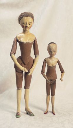"""18th Century Wooden Doll with Shaped Body18"""" (46 cm). One piece carved wooden head and torso, sculpted bosom inside carved suggestion of stomacher, dowel-jointing at shoulders, elbows, hips & knees, carved heeled shoes, painted-over-gesso complexion & facial features, downcast brown eyes. 18th century, Continental. Exceptional doll whose rarity points include characterized facial features, sculpted stomacher, beautifully shaped legs w painted shoes, modeled bosom."""