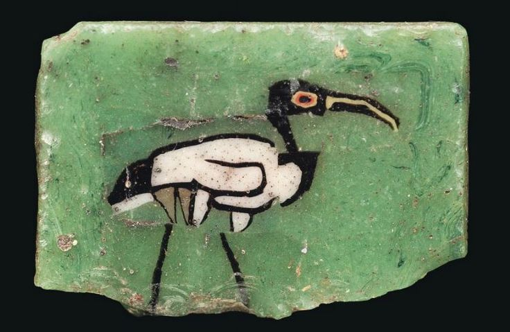 Egyptian mosaic glass ibis inlay, 1st century B.C.-1st century A.D. The translucent amethyst body with opaque white wing, translucent yellow legs, red circled eyes and yellow beak in green matrix, 1.9 cm long. Private collection