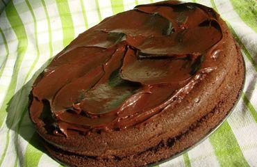 Všechny ingredience na těsto smícháme šlehačem a nalijeme do máslem vymazané formy. Pečeme ve vyhřáté troubě na 180°C přibližně 30 minut. Vyjmeme a necháme úplně vychladnout. Mezitím co nám korpus chladne, nad vodní lázní rozpustíme máslo s čokoládou. Velmi pomalu, aby se nám čokoláda nepřipalovala. Poté z lázně odstavíme, necháme trochu vychladnout a do vychladlé směsi jemně vmícháme ostatní ingredience na náplň a polevu. Vychladlý korpus rozkrojíme na půl a na spodní část korpusu namaže...