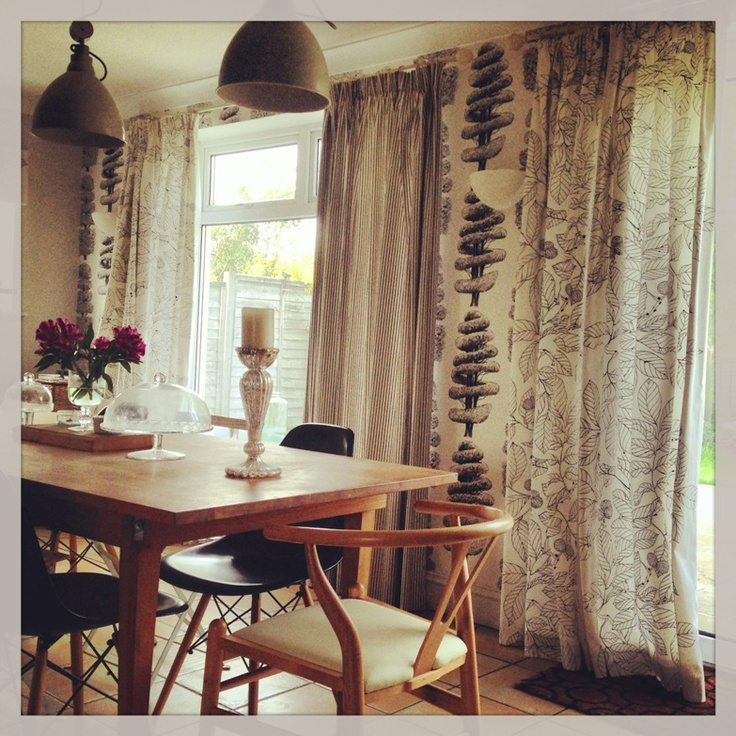 pencil pleat curtains in monochrome mismatched fabric give a relaxed and contemporary feel to this kitchen/diner.