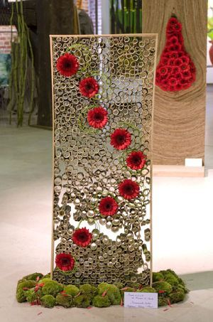 Hollow branches (bamboo) were cut into little pieces and with hen fence created to a frame. In this frame red gerberas (Suri) were put in a artistic way. Altogether a very airy arrangement was created. At the ground pieces of moss were put as a base.