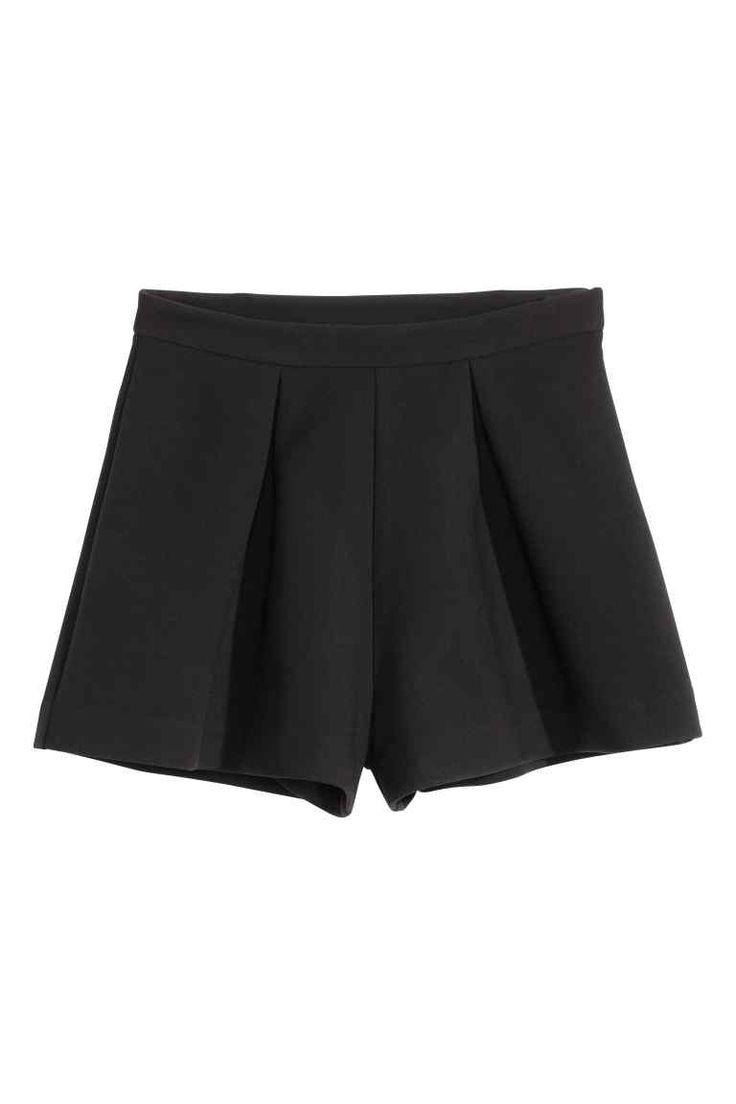 Calções largos: Calções curtos e largos em tecido stretch grosso. Têm pregas na cintura e fecho éclair oculto de lado.