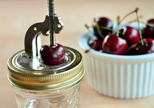 Inexpensive cherry pitter that *works*! Clamps to top of canning jar; hole allows pit to fall through while cherry stays on top.