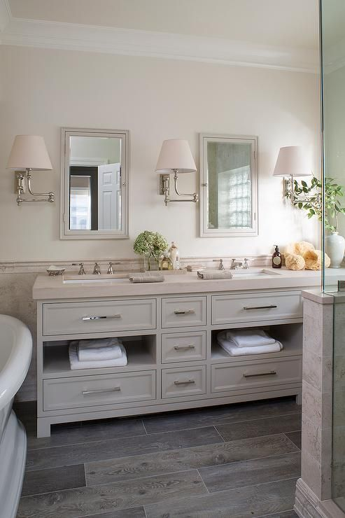 Cream and gray bathroom features top half of walls painted cream and bottom half of walls clad in ...