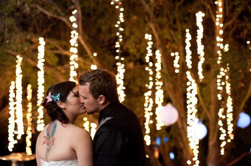 hanging twinkle lights and paper lanterns under a large oak tree