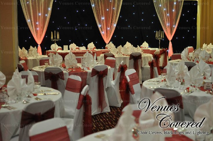 www.venuescovered.co.uk White chair covers with garnet organza sashes, favours, black starlit backdrop and red uplighting