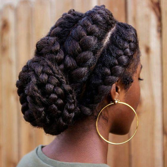 Quatre tresses plaquées en chignon bas sur des cheveux afro