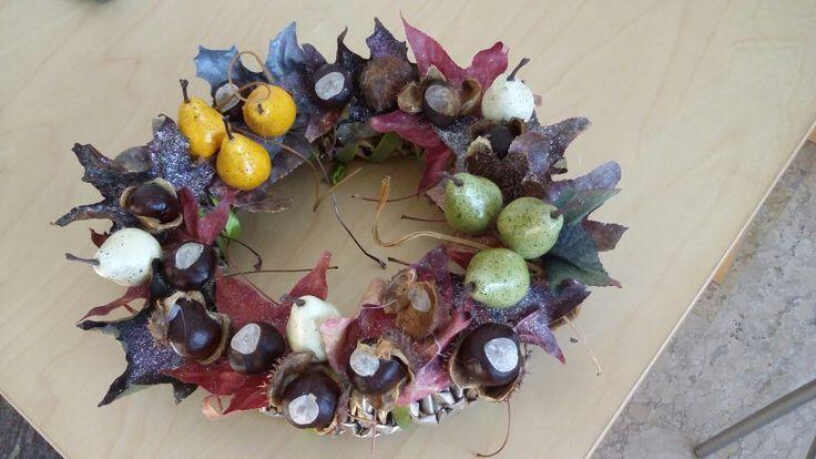 Ghirlanda autunnale creata con carta di giornale e decorata con quello che la natura ci offre in questa stagione