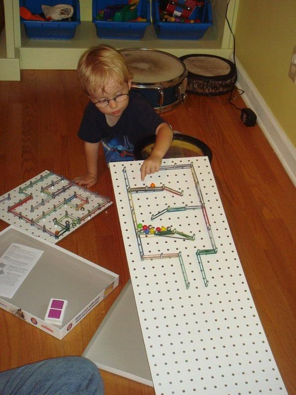 Simple Rube Goldberg Machine for Kid - DIY marble maze using pegboard on an incline, colorful rubber bands, and marbles. The goal was to hit and topple as many foam pieces (inside the box) as possible. 16 Cool Rube Goldberg Machine Ideas, http://hative.com/rube-goldberg-machine-ideas/,