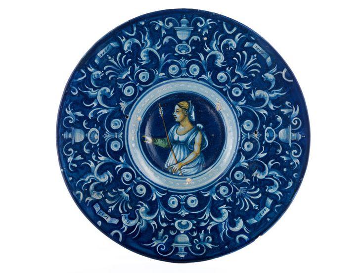 Der flache Teller mit breiter Fahne. Im Spiegel ist eine junge Jägerin im Profil nach links dargestellt. Mit einer Hand weist sie nach vorne, die andere hält ...
