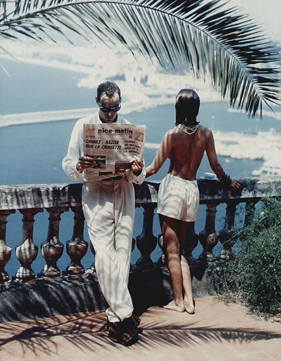 Guy reads newspaper and lady looks at the seaside, terrace view