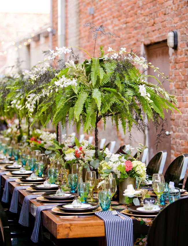 Potted ferns are lush and inexpensive.  Elevate them and incorporate vines of orchids or your favorite flowers for impact and affordability.