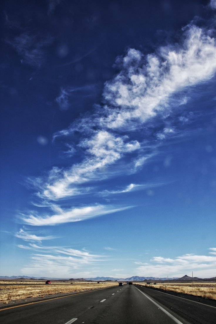 Cirrus Clouds over Empty Black Road  Free Stock Photo