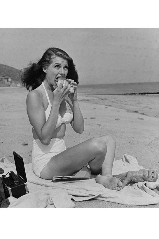 Rita Hayworth in Santa Monica  In 1941, 'goddess of love' Rita Hayworth, took a Californian lunchbreak and posed for the lens of Bob Landry. Appearing in Life magazine, the resulting editorial featuring the bikini-wearing beauty on the Santa Monica beach gained worldwide recognition. With her white two-piece, her hair in the wind and a sandwich in hand, Rita Hayworth became one of the most popular pin-ups of the 1940s.  By Eugénie Trochu, translated by Quinn Connors