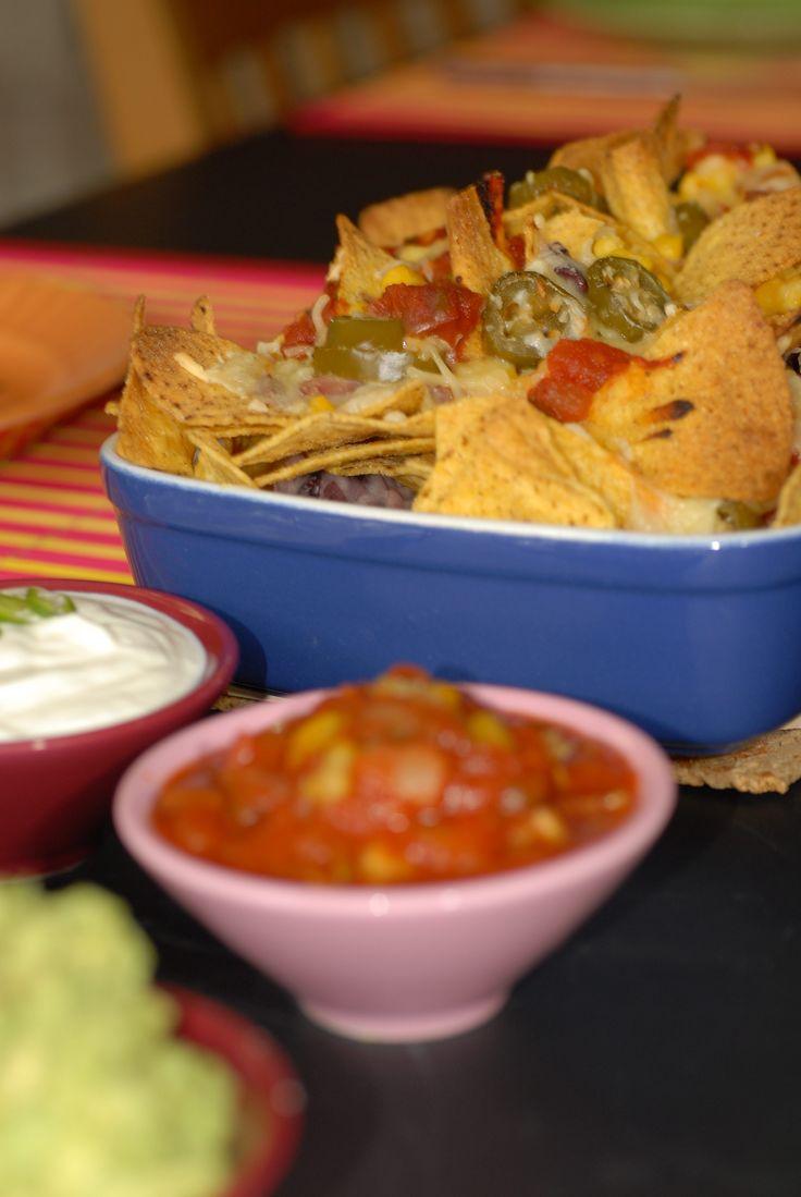 Ostgratinerade nachos med bönor, ett måste till fredagsmyset! Heta jalapeños blir supergott till söt majs och krämig ost. Här hittar du vårt enkla recept.