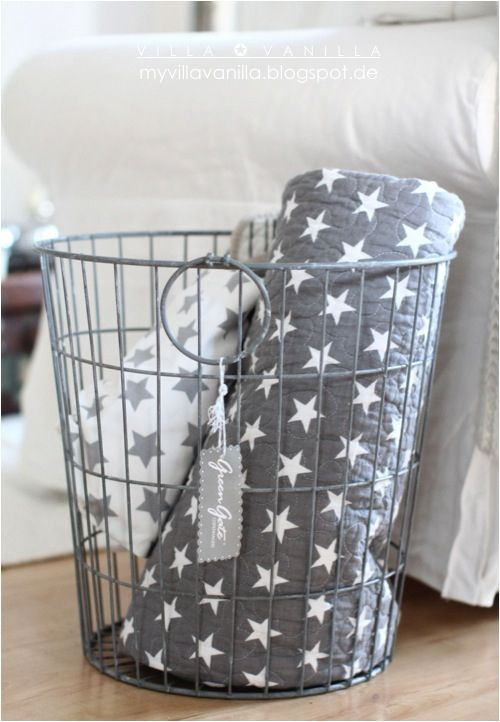 starred throws in a wire basket beside sofa | S T A R S ...