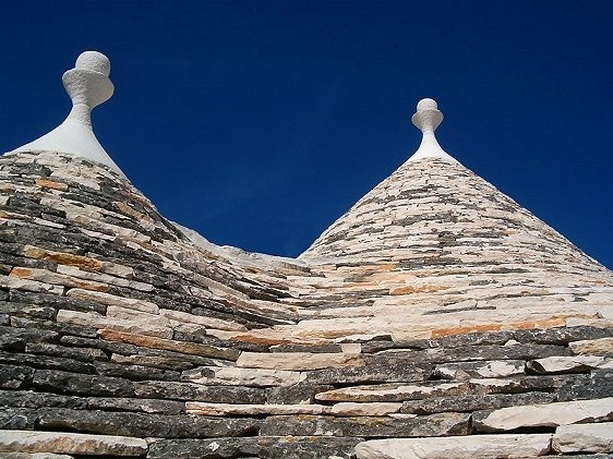 Apart from the town of Alberobello, they can also be seen in Locorotondo, Fasano, Cisternino, Matina Franca and Ceglie Messapica. The conical roofs are constructed in two layers. The inner layer is of limestone boulders capped by a keystone. The outer layer are limestone slabs that help keep the abode watertight. The trulli in Alberobello are topped with a pinnacle and their roofs are often painted with symbolic designs.