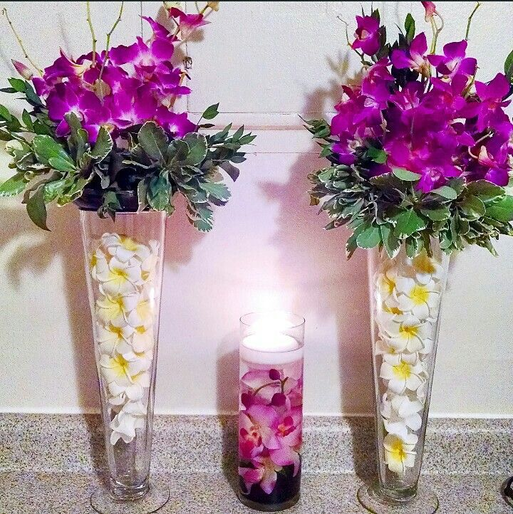 Tall purple orchid and plumeria centerpieces floating
