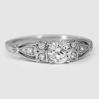 This vintage-influenced ring features a dazzling center diamond with six round accent diamonds in a sculpted design. #BrilliantEarth