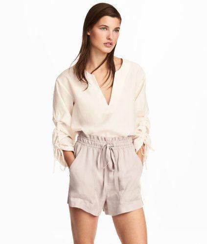 Ljus mullvad. CONSCIOUS. Ett par vida shorts i vävd kvalitet av Tencel® lyocell. Shortsen har hög midja med resår och dragsko samt sidfickor. Volangkant