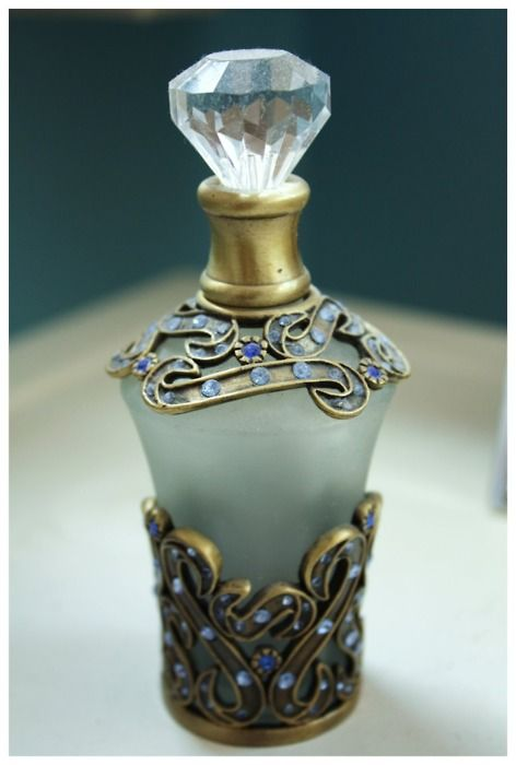Opaque glass perfume bottle with brass filigree base and collar set with small blue gems.