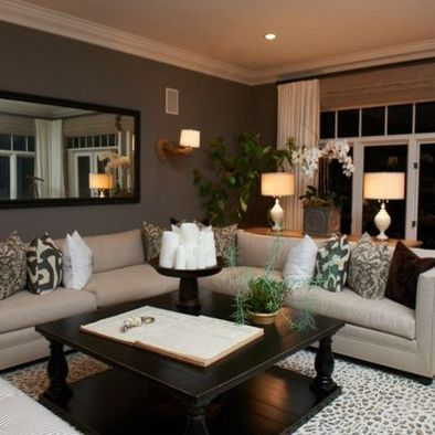 Family room decor. Dark wall paint. Sconce. Mirror to make room appear larger and spread light. Cream sectional sofa for lots of seating. Printed rug. Large coffee table in dark wood. Sofa table with pair of white base lamps. Several organic items such as plant, flowers, tree. Mixed print pillows on sofa. Straw roman shade. White drapes. Crown molding. Large coffee table book.