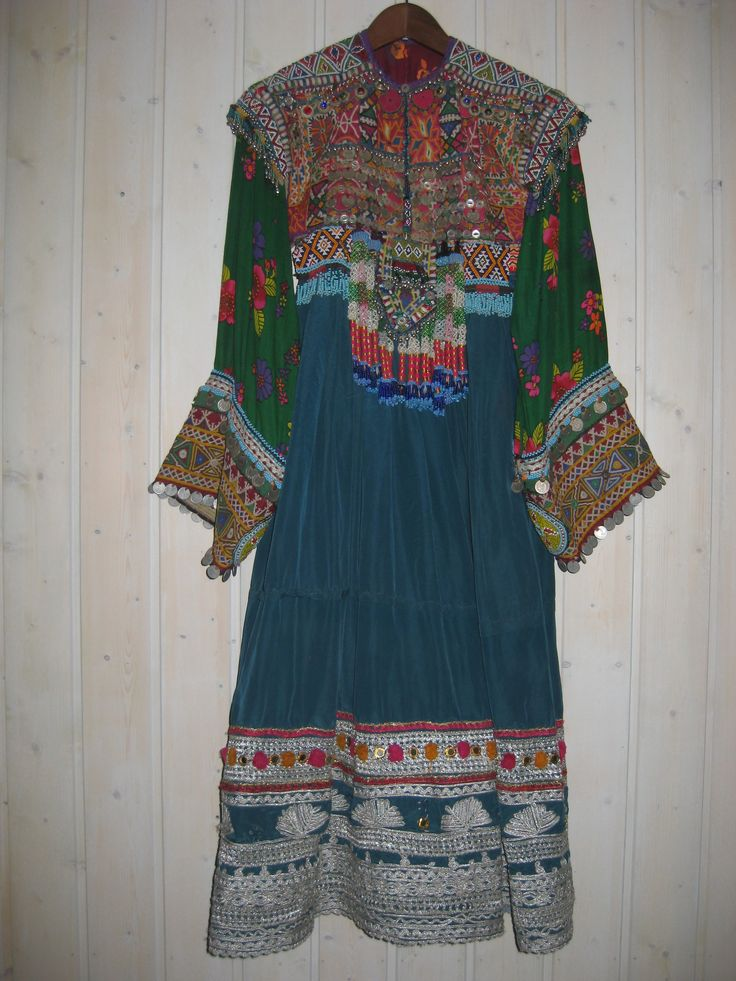 Woman's dress. The Kochi are nomadic herders and gypsies and their clothing is particularly flamboyant. Their dresses, brought back to the West, are those that identified Afghanistan in the 1970s hippie era. This dress is of lue cotton. The embroidery includes fine interlacing in yellow. The bodice is heavily covered with coins and beadwork, including jul-i-peron discs; while these have an ancient history, the silver cording on the hem is modern.