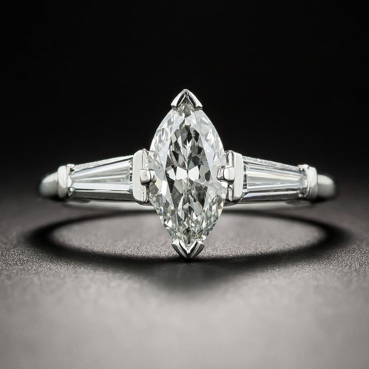 An elegantly proportioned, bright white and sparkling marquise-cut diamond, weighing 1.07 carats, sizzles between a pair of tapered baguette diamonds in this sleekly streamlined engagement ring, hand-fabricated in platinum during the mid-twentieth century. Accompanied by a GIA Diamond Grading Report stating: I color - SI1 clarity. A chic and sophisticated ultra-sparkler. Currently ring size 6 3/4.