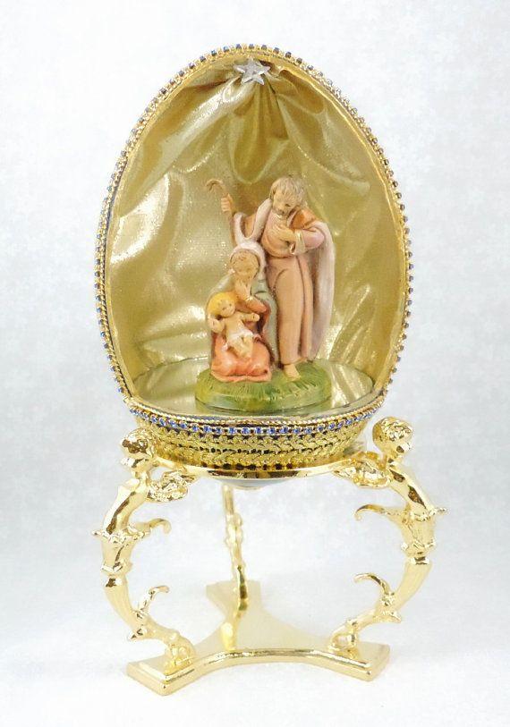 Dieses schöne Krippe zeigt Maria mit Jesuskind mit Joseph über ihnen stehen. Erstellt von ein handgemaltes Rhea Ei. Die Vorderseite des Eies in einem Oval mit einem quadratischen weggeschnitten ist vom Boden. Die Kante ist verschwenderisch mit Gold schnüren, Saphir Swarovski Perle Kette und Gold Bullion Geflecht getrimmt. Innerhalb einer Hand ist gemalte Figur der Maria, Josef und Jesuskind eingeschaltet ein großer Spiegel, schimmernden Hintergrund Gold lame. Ein Kristall Swarovski Stern…