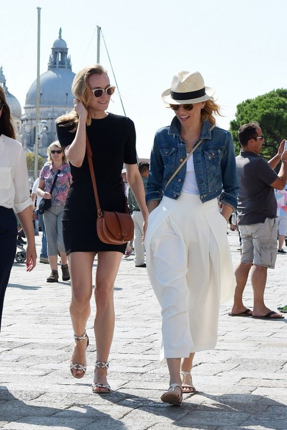 Diane Kruger donning a brown leather crossbody bag and black t-shirt dress seen with Elizabeth Banks who is wearing a white tank tucked into a flowy cream skirt, and a jean jacket.