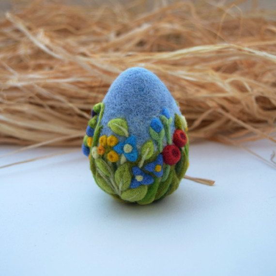Easter Egg Needle Felted Eggs Home Decor Easter Ornament Some 'bunny' loves you! This captivating royal blue felted Easter egg ornament is a whimsical decor accent for an Easter basket or even to display in your home. Custom handmade by a seasoned artisan, it is wool felted and sized to look like a real egg. The exterior features a stunning array of greenery and spring flowers that are vividly colorful. You can place it on the table to accentuate your centerpiece or buy several to fill a…