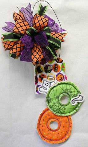 """A B-O-O door hanger with a happy little ghost peaking out. This is the perfect size and lightweight for your Halloween decor, all tied with a multi-patterned Terri Bow. Measures 30""""H X 14""""W."""