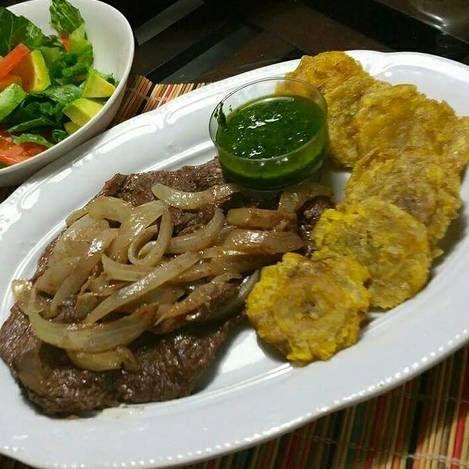 Bistec de res encebollado, acompañado con salsa de cilantro.