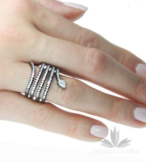Ciekawy pierścionek obrączka wykonany ze srebra próby 925 w kształcie węża. Wyrób oksydowany i rodowany, wysadzany białymi Cyrkoniami (tzw. microsety). Pierścionek w formie sprężyny w rozmiarze 13, ale istnieje możliwość dopasowania go o jeden rozmiar czyli 12 lub 14. Szerokość wzoru w obrączce to 2,3 (od głowy węża do ogona).   Polecamy ten wyrób szczególnie miłośniczkom najnowszych trendów i ciekawych stylizacji.