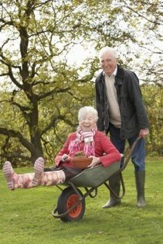 Older couple having fun. I guess your Never too old for a wheelbarrow ride in the garden…