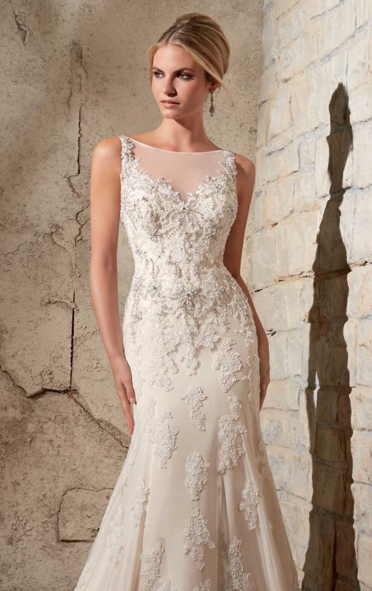 Grace your wedding in Bridal by Mori Lee 2709. This beautiful wedding gown features a sheer bateau neckline with open v-back. Crystal beaded embroidery accentuates the rich lace and net that covers the flattering silhouette. This exquisite gown is trimmed with a fit and flared skirt, with sweep train that cascades to the full-length hemline creating a superb look. This style can also be ordered in 55 inches and 58 inches. Please contact us if you would like to customize the length.