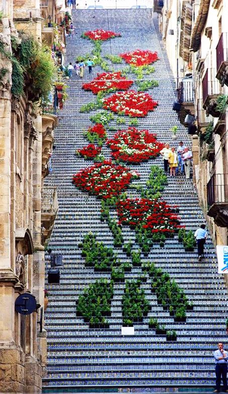 Street Art...La Scala di Santa Maria del Montem, Caltagirone, Sicily, is an old 142-step staircase, each of which are decorated with a different ceramic pattern. It's a wonder to behold, but during the Spring and Summer seasons it becomes even more breathtaking as locals adorn it with potted flowers and lanterns, creating intricate designs. Photo by Andrea Annaloro.