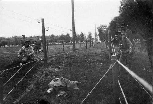 The 'Wires of Death'. Barbed wire entanglement at the border between the Netherlands and Belgium during the First World War near Sluis in Zeeland. German soldier posing as casualty. 1915.