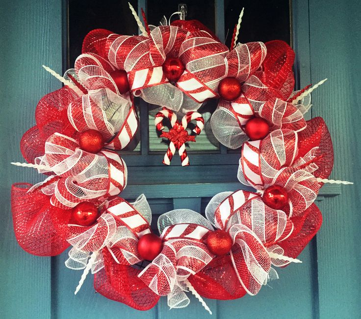 """Wire wreath frame covered with red and white mesh intertwined with """"candy cane"""" (red & white stripped) mesh. Shiny, glitter and matte red ornaments along wi"""